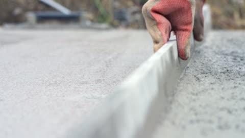 vídeos y material grabado en eventos de stock de manos de un trabajador de base de hormigón de nivelación - material de construcción