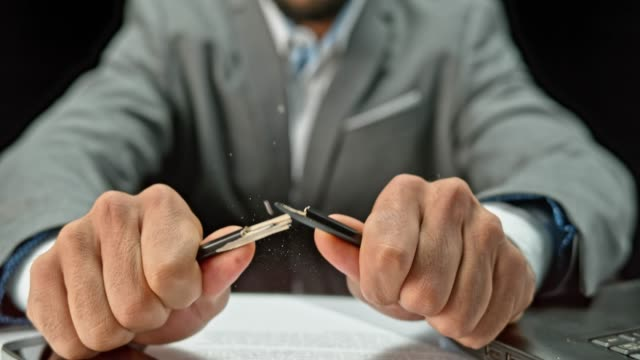 slo mo ld hands of a young businessman breaking a pencil - rompere video stock e b–roll