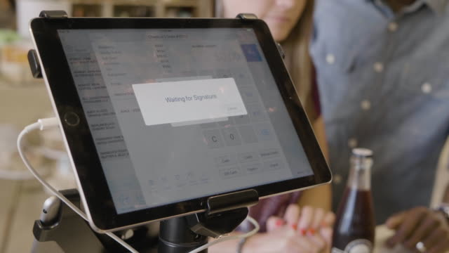 hands of a young caucasiuan store clerk enters a purchase of non-alcoholic soda beverage on an ipad payment system at a neighborhood market and wine shop. - touch sensitive stock videos & royalty-free footage