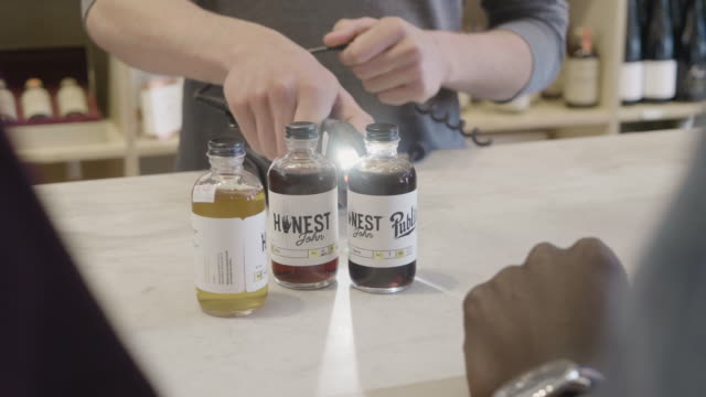 stockvideo's en b-roll-footage met hands of a young caucasiuan store clerk scans and rings up a purchase of non-alcoholic bitters at a neighborhood market and wine shop. - financieel item