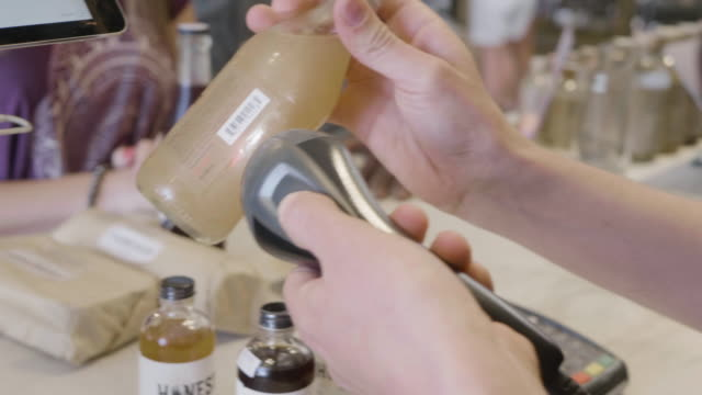 stockvideo's en b-roll-footage met hands of a young caucasiuan store clerkuses a bar code reader to scan and rings up a soda purchase at a neighborhood market and wine shop. honest john brand bitters visible as purchase. - financieel item