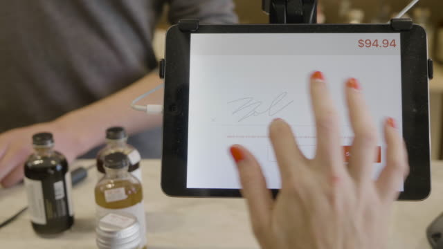 vídeos de stock e filmes b-roll de hands of a young female caucasiuan customer as she signs for a credit card purchase on an tablet computer payment system at a neighborhood market and wine shop. - ecrã tátil