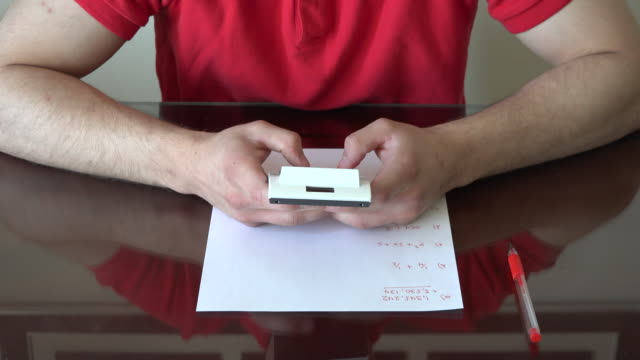 vidéos et rushes de hands of a young man using a calculator while studying math - niveau collège lycée