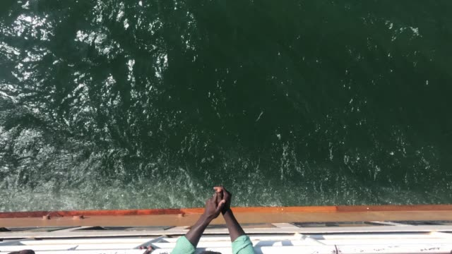 vídeos de stock e filmes b-roll de hands of an african man lay on the side of a ship - ferry