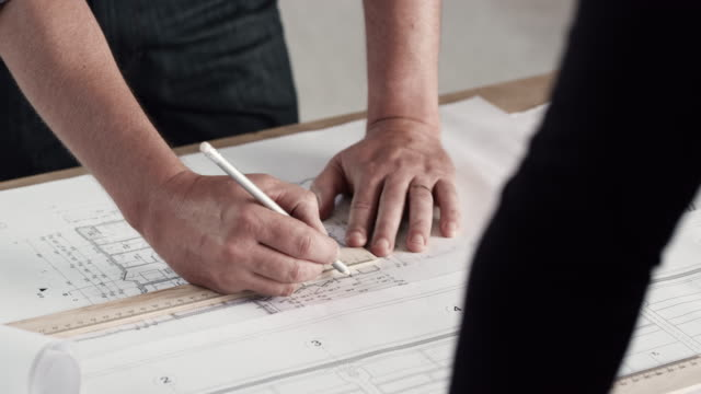 Hands of an architect making notes and alternating the plans on the table while talking to someone