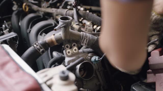 vídeos y material grabado en eventos de stock de manos de auto mechanic cambio y reparación cool radiator cool coolante en garaje. - nevera portátil