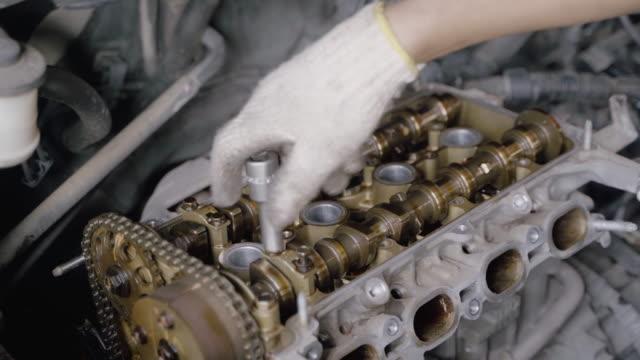 vidéos et rushes de mains de mécanicien automatique collaborer clé à la réparation et la soupape moteur d'entretien du bloc cylindre. - membres du corps humain