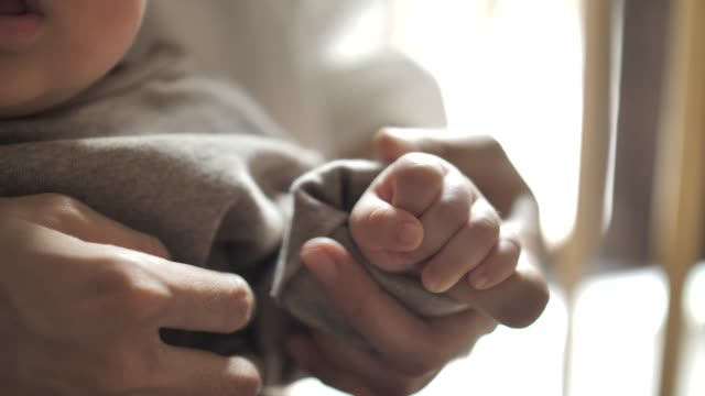 hands of baby holding mother hand closeup, hand in hand. mother care - pregnant stock videos & royalty-free footage