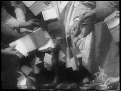 B/W 1961 hands of Black people burning passbooks in bonfire / South Africa / newsreel