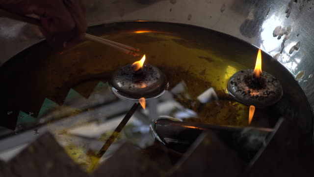 Hands of buddhist holding incense sticks in the oil fire tank