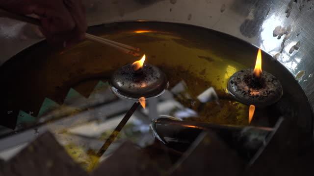 Händen der buddhistische Räucherstäbchen in den Öltank Feuer halten