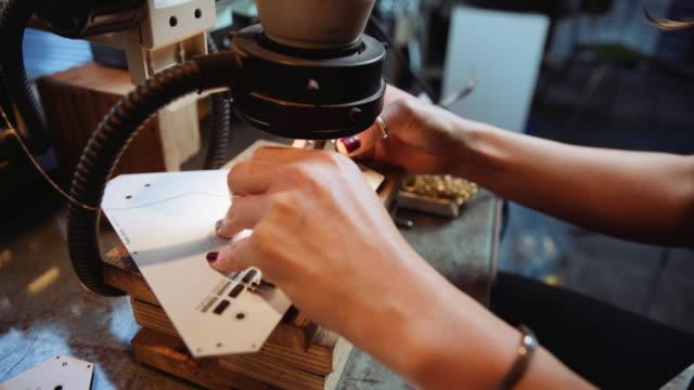 vídeos y material grabado en eventos de stock de hands of chinese woman soldering under microscope in workshop - esmalte de uñas rojo