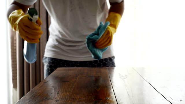 手のクリーナー スプレーで木製のテーブルを掃除やマイクロファイバーの布で拭き取り - 片付いた部屋点の映像素材/bロール