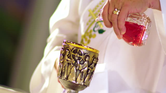 vidéos et rushes de cu canted hands of deacon pouring wine and water into chalice at altar, manhattan beach, california, usa. - prêtre