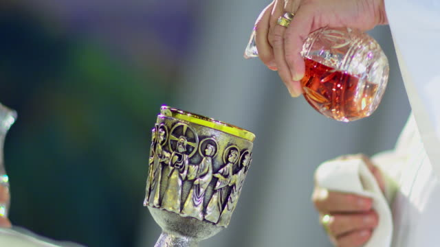 CU CANTED Hands of deacon pouring wine and water into chalice at altar, Manhattan Beach, California, USA