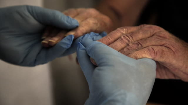 hands of doctor in hospital during coronavirus crisis, wearing blue surgical gloves, holding hands of patient, manchester - close up stock videos & royalty-free footage