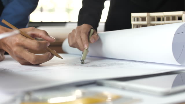 vídeos de stock e filmes b-roll de hands of engineer discussion on blueprint - arquiteta