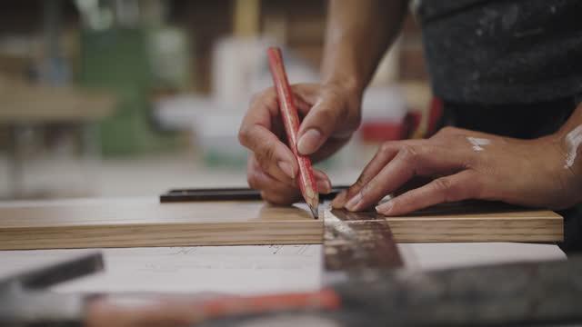 vídeos y material grabado en eventos de stock de hands of female carpenter drawing on plank with pencil at workshop - carpintería