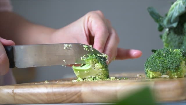 hands of female chef cutting broccoli on a wooden cutting board - broccoli stock videos & royalty-free footage