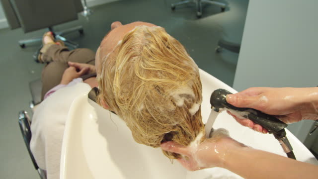 ha ms hands of female hairdresser rinsing reddish hair of mature woman - legs crossed at ankle stock videos & royalty-free footage