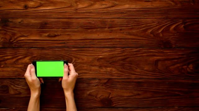 vídeos de stock, filmes e b-roll de mãos de mulher segurando um telefone sobre fundo de madeira - copy space