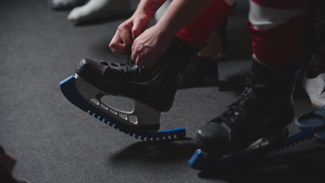 Hands of female ice hockey player tying skates before practice
