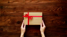 Hands of female placing a present box on a wooden background