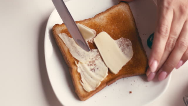 hands of female spreading butter and jam on a slice of bread - bread stock videos & royalty-free footage