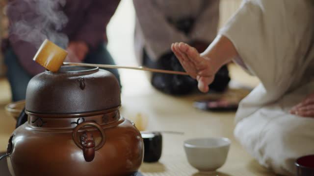 vídeos y material grabado en eventos de stock de manos del anfitrión de la ceremonia del té japonesa moviéndose entre implementos - sado