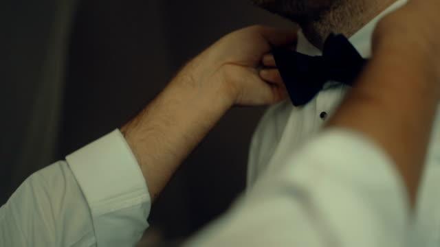 CU handen van man bruidegom bowtie aanpassen