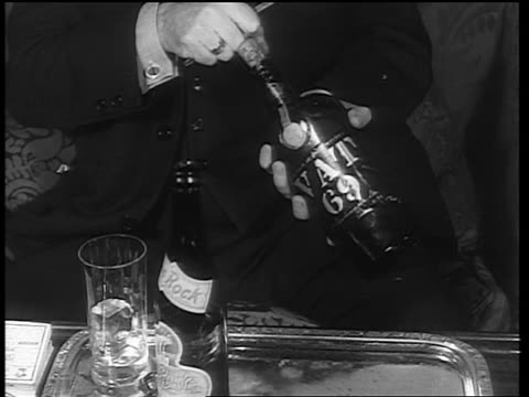 b/w 1933 hands of man popping cork from bottle labeled vat 69 / end of prohibition - anno 1933 video stock e b–roll