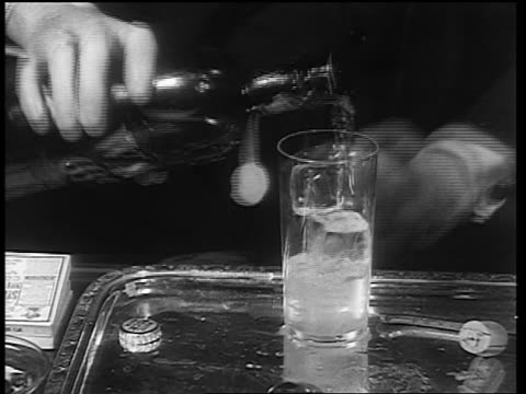 b/w 1933 hands of man pouring from bottle labeled vat 69 into glass / end of prohibition - 1933年点の映像素材/bロール
