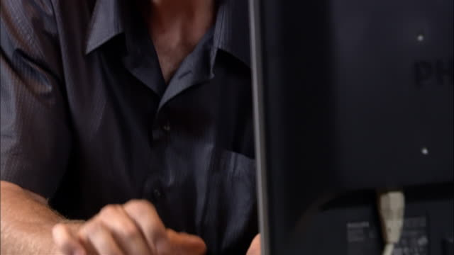 Hands of man typing on desktop computer / tilt up to man looking at monitor / nodding head and smiling