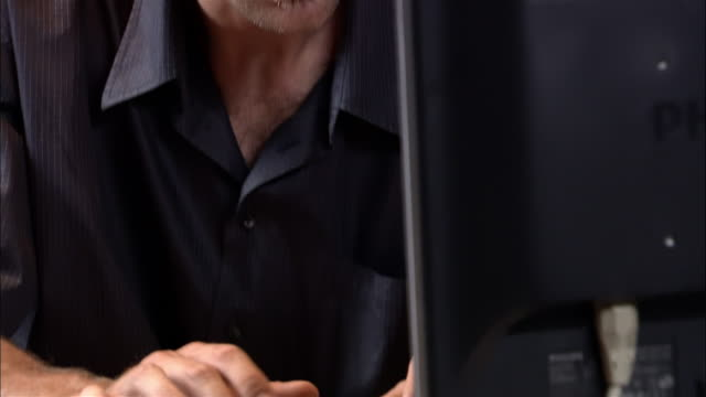 Hands of man typing on desktop computer / tilt up to man looking at monitor, running hands through hair, and shaking head in dissatisfaction