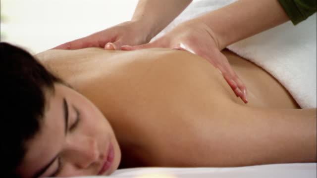 stockvideo's en b-roll-footage met hands of massage therapist rubbing massage oil into palms / massaging woman's back - menselijke rug