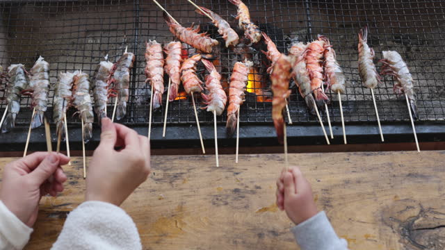 hands of mother and daughter grilling shrimps on the grill - offbeat stock videos & royalty-free footage