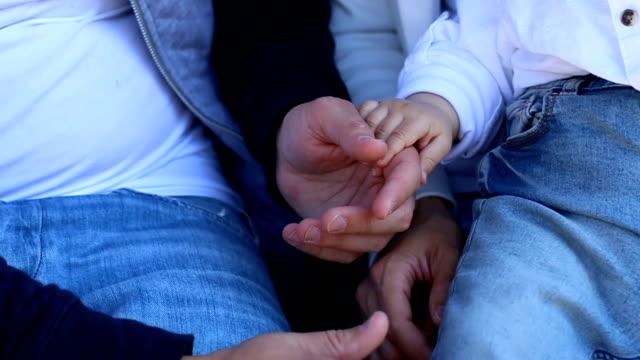 Händen der Mutter Vater und Baby hautnah