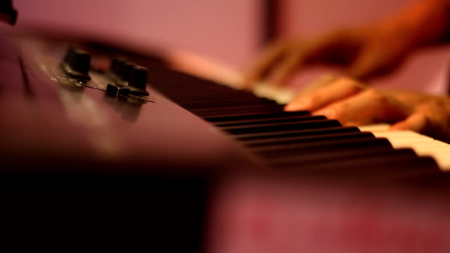 vídeos de stock e filmes b-roll de hands of musician playing keyboard in concert with shallow depth of field - pianista