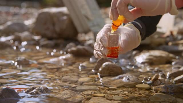 vídeos y material grabado en eventos de stock de manos de persona usando guantes y añadiendo un reactivo a la muestra de agua tomada del río - reacción química
