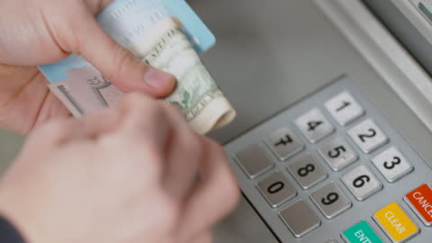 vídeos de stock e filmes b-roll de hands of person withdrawing money at an atm, taking it out of the dispenser slot - making money