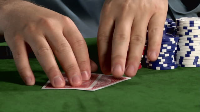 vídeos de stock, filmes e b-roll de hands of poker player catching cards being dealt across table / looking at cards / placing red chip on top of cards / placing bet - pôquer