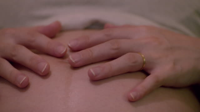 CU,Hands of pregnant woman caressing her belly.