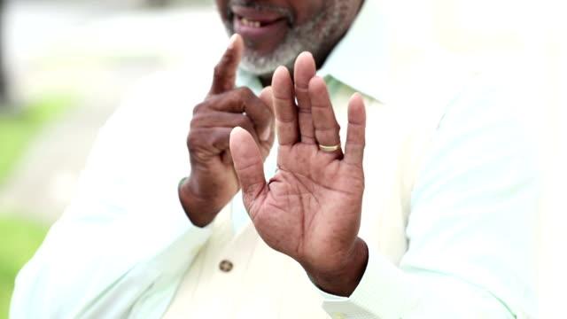 お小言を食いを与えるアフリカ系アメリカ人の年配の男性の手 - 部分点の映像素材/bロール