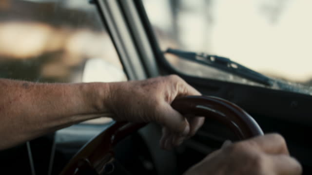vídeos de stock e filmes b-roll de hands of senior man on steering wheel, driving on rural road - one senior man only