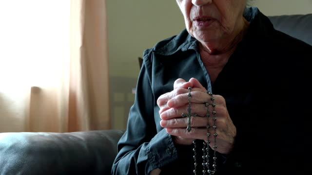 vídeos de stock e filmes b-roll de mãos de mulher idosa rezar com rosary ou crucifixo - benção