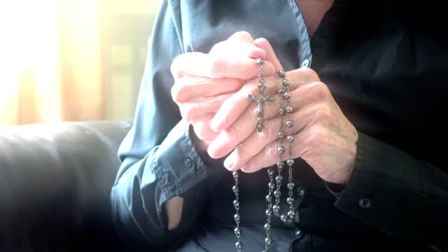 vídeos de stock, filmes e b-roll de mãos da mulher idosa com do terço ou crucifixo orar - mulheres idosas