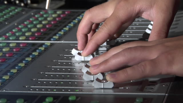 CU Hands of sound engineer adjusting volume on mixing console / New York City, New York, USA