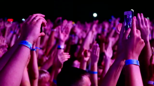 vídeos de stock e filmes b-roll de hands of spectators at a rock concert with smartphones - evento de entretenimento
