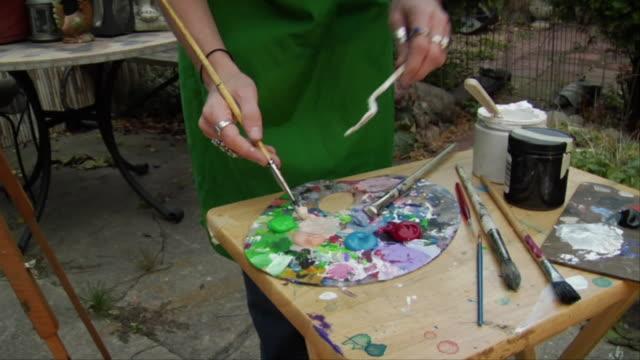 stockvideo's en b-roll-footage met cu, zi, hands of teenage girl (16-17) mixing paints on palette, brooklyn, new york city, new york, usa - verfkwast