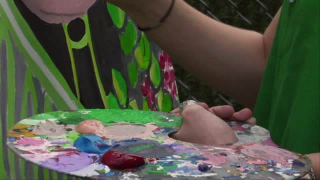 CU, Hands of teenage girl (16-17) painting in garden, Brooklyn, New York City, New York, USA